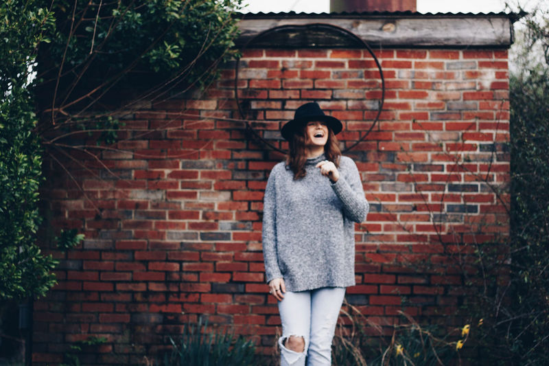 Women Around The World Brick Wall One Person Contemplation Standing Outdoors Red Building Exterior People Young Adult Day One Young Woman Only Adults Only Adult Only Women One Woman Only Beautiful Woman Adults Only Women Beauty Hipster - Person Toothy Smile Cheerful Happiness City Life