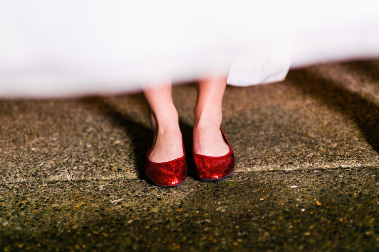 Low section of woman wearing red sequin shoes standing on footpath