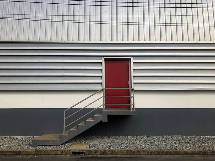 The Warehouse Exterior with Red Door and Stairs Design