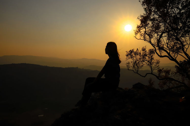 Silhouette woman sitting on rock against sky during sunset