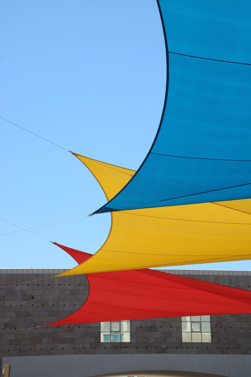 LOW ANGLE VIEW OF YELLOW FLAG AGAINST BLUE SKY