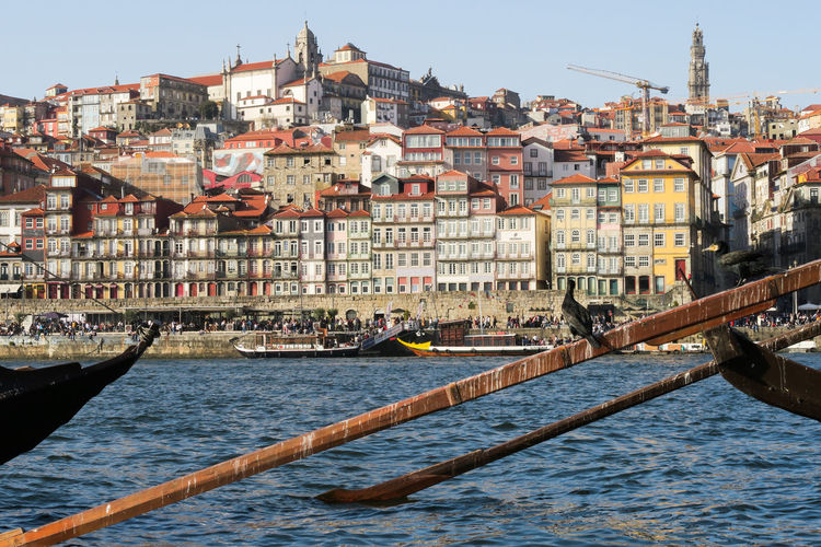 bird sitting on the pedal of a rabelo boat in front of porto old town, portugal Pedal Douro River Old Town Cityscape Porto Portugal Sunny Springtime Spring Vacation Calm Cityscape City Water Nautical Vessel Sky Architecture Building Exterior