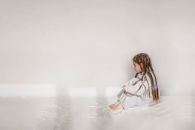 Girl with braided hair sitting on bed against white wall