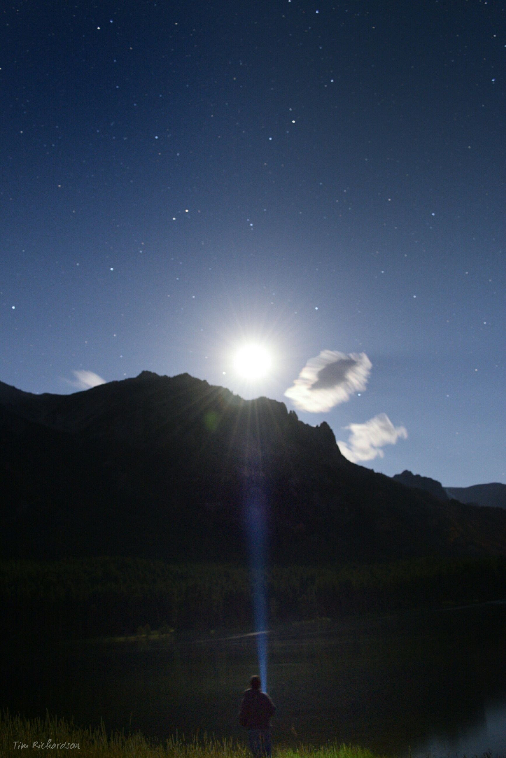 tranquil scene, scenics, tranquility, beauty in nature, mountain, sky, silhouette, nature, sun, landscape, idyllic, mountain range, night, majestic, astronomy, lens flare, moon, non-urban scene, sunlight, star field