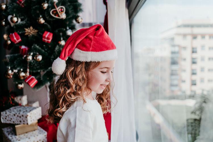 Smiling girl wearing santa hat looking through window at home