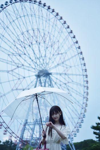 Portrait of woman with ferris wheel against sky