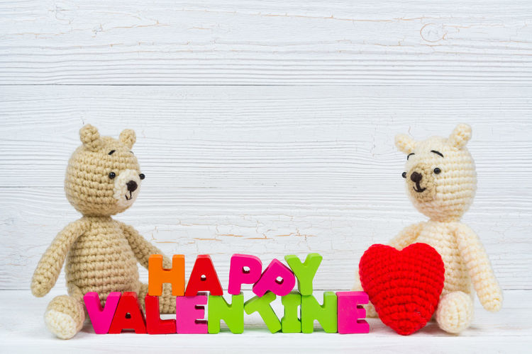 Sweet couple teddy bear doll in love with valentine text and red knitting heart on white wooden background and copy space for add text and picture, love and valentine day concept idea. Toy Animal Representation Representation Stuffed Toy Teddy Bear Childhood Indoors  Cute Animal Art And Craft Creativity Still Life Wood - Material Toy Animal Mammal Table Multi Colored Studio Shot Textile Softness
