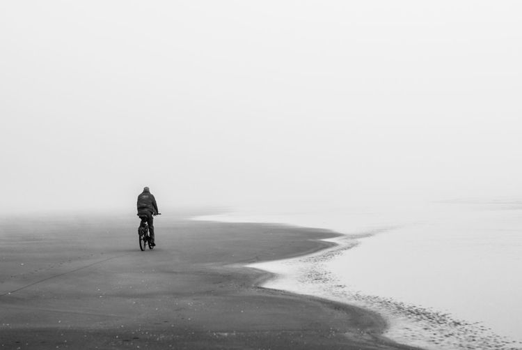 Rear View Of Man Riding Bicycle At Beach During Foggy Weather