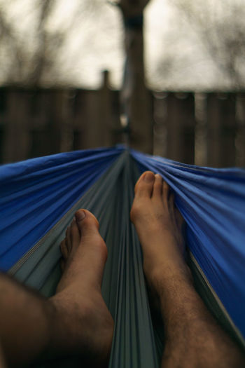 Low section of man resting on hammock