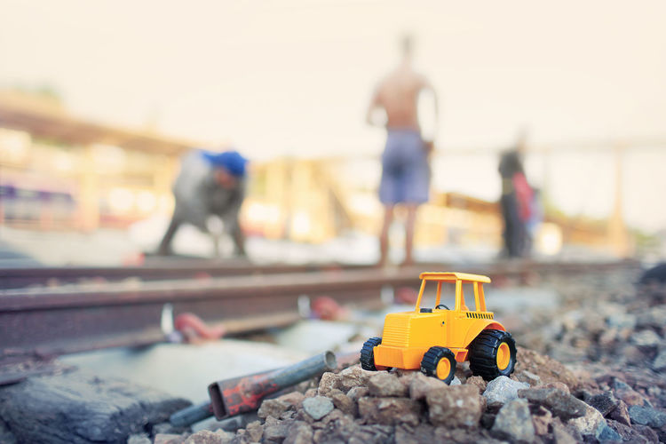 Close-up of toy with people working on railroad track against sky