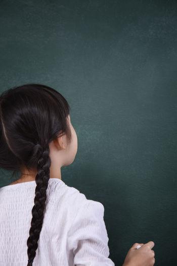 Rear View Of Girl Writing On Blackboard