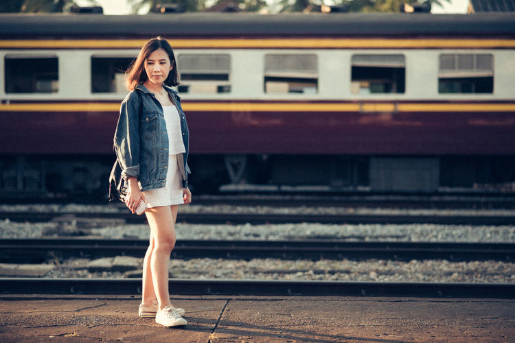 Young Woman Standing At Railroad Station