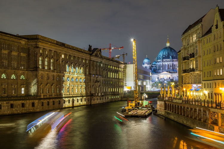 Light trails on canal by illuminated berlin cathedral against sky at night
