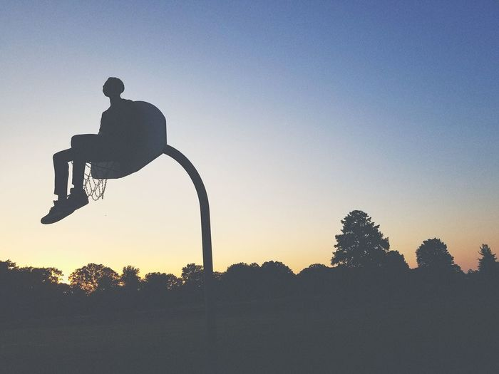 Low angle view of silhouette man sitting on basketball hoop against clear sky