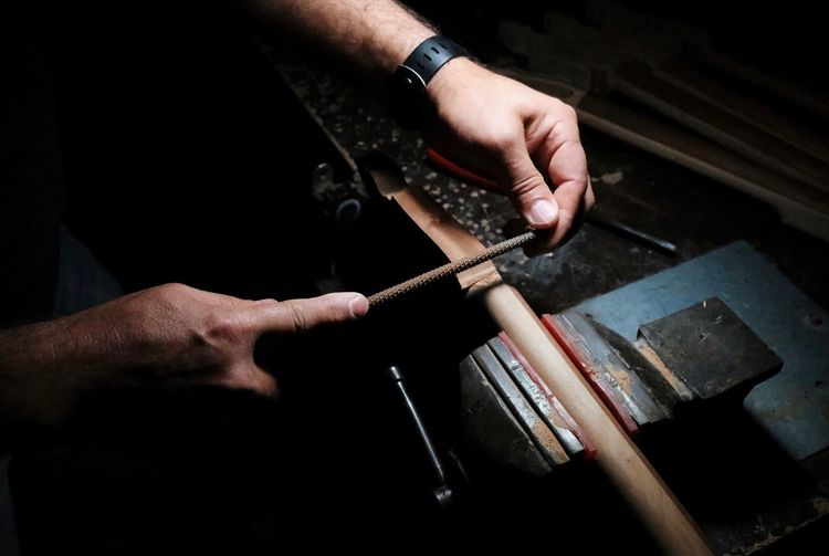 Cropped hands of craftsperson holding metal while working at workshop