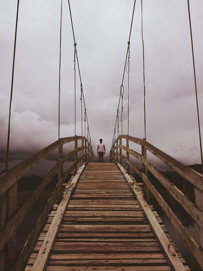 Man standing on footbridge against sky