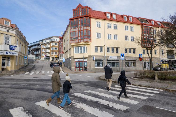 People walking on road by buildings