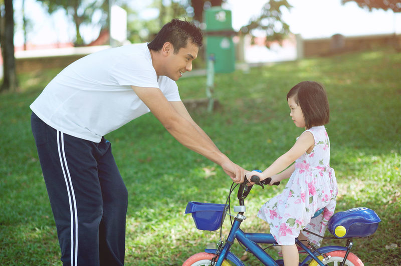 family time father and daughter Helping Adult Bicycle Bonding Casual Clothing Cheerful Childhood Cycling Daughter Day Family With One Child Father Grass Happiness Leisure Activity Lifestyles Outdoors People Real People Smiling Togetherness Young Adult