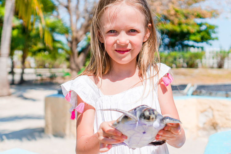 Portrait of cute girl holding turtle