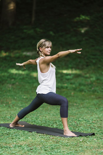 Young Woman Doing Yoga, Warrior Pose Beautiful Blonde Exercise Grass Green Nature Slim Yoga Yoga Pose Yoga Nature Young Balance Caucasian Forest Healthy Lifestyle Outdoors Practising Raising Relax Vertical Vitality Warrior Pose Yoga Outside Yoga Retreat Yoga Woman
