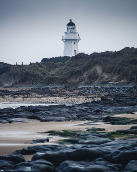 Lighthouse Architecture Beach Building Building Exterior Built Structure Direction Guidance Land Lighthouse Nature No People Outdoors Protection Rock Safety Sea Security Sky Solid Surface Level Tower Water