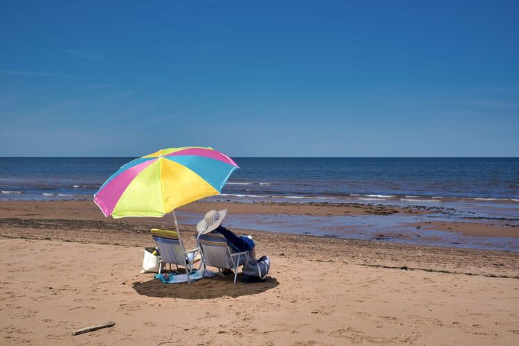Canada, PE: Cousins Shore beach Clear Sky Daytime From Behind Hat Moment Panoramic Relaxing Summertime Woman Beach Beach Umbrella Beauty In Nature Blue Canada Chair Clear Sky Colorful Cousins Shore Day Daylight Horizon Horizon Over Water Land Nature No People One Person Only Outdoors Parasol Prince Edward Island Red Sand Relax Sand Sandy Scenics Scenics - Nature Sea Shade Sky Summer Umbrella Unrecognizable Person Water Woman With Hat