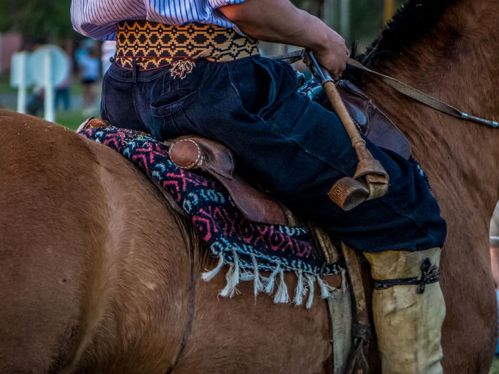 Midsection of man riding horse