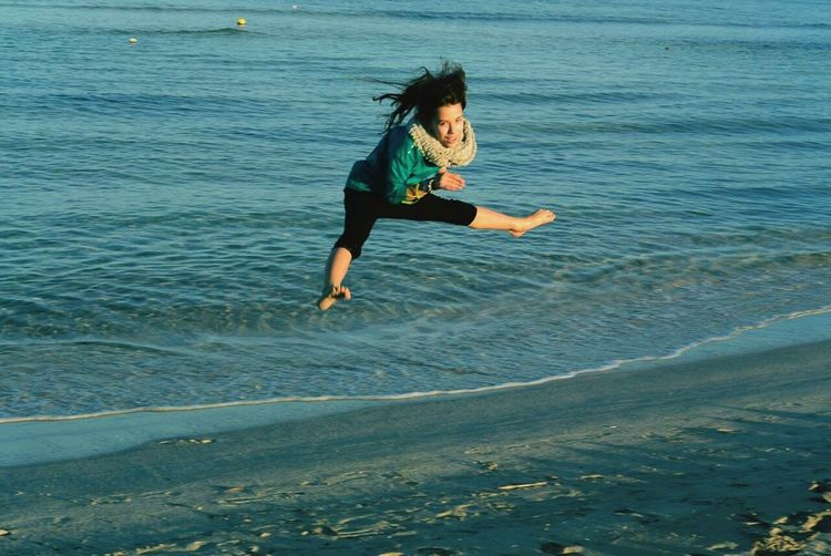 Portrait of excited woman jumping with legs apart at beach