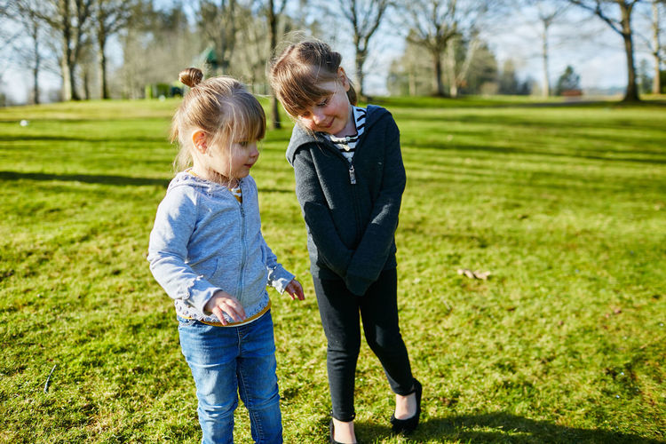 Grass Child Childhood Two People Togetherness Family Plant Full Length Casual Clothing Females Bonding Day Emotion Standing Nature Women Innocence Hair Jeans Outdoors Sister Girl