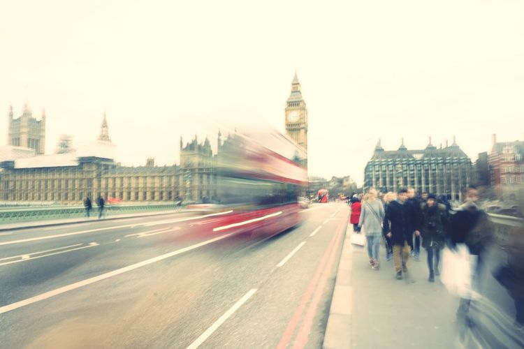 Blurred motion of people and bus on westminster bridge