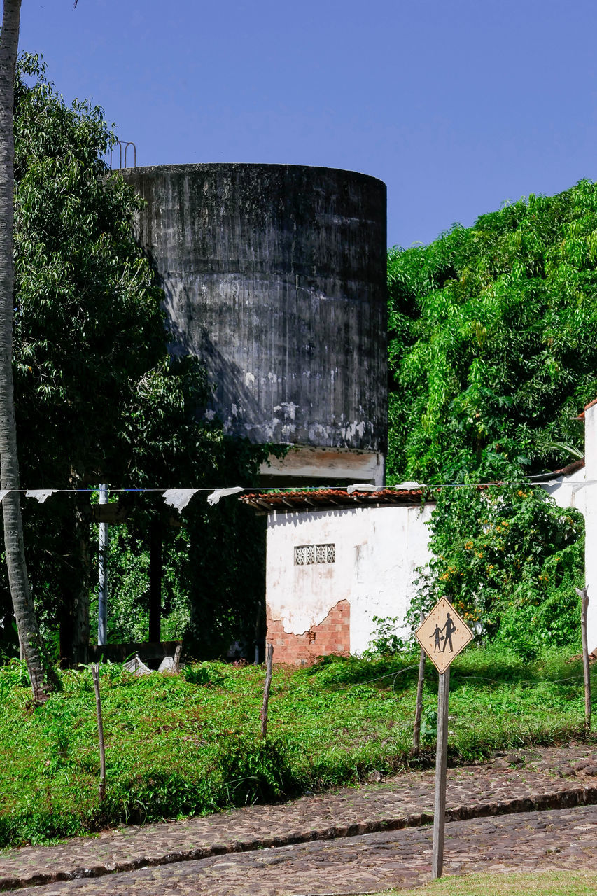 tree, architecture, text, day, built structure, communication, no people, outdoors, clear sky, nature, water tower - storage tank, sky