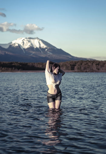 Young woman with arms raised standing in lake against snowcapped mountain