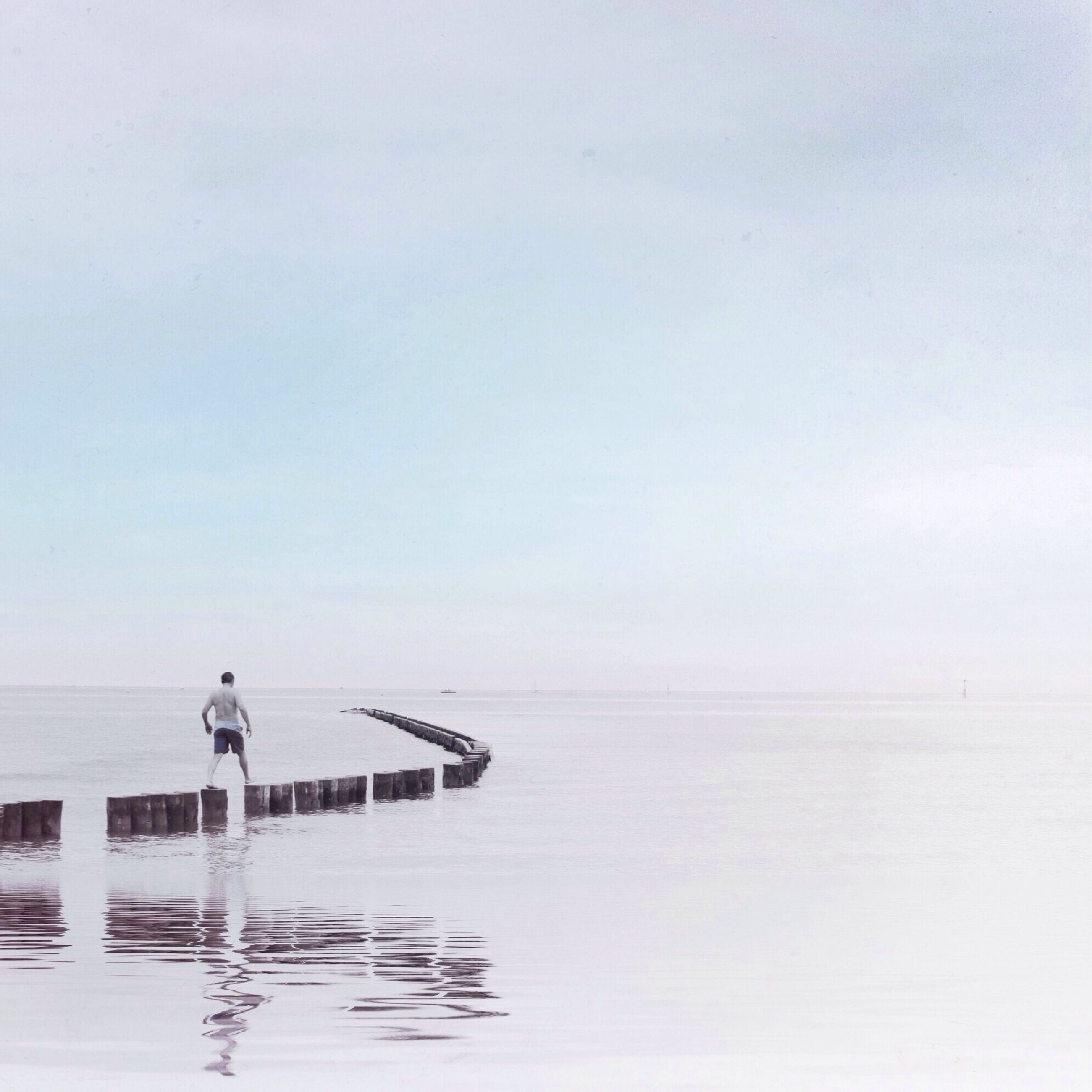 water, sea, lifestyles, copy space, leisure activity, clear sky, horizon over water, tranquil scene, tranquility, full length, rear view, standing, scenics, men, pier, nature, beauty in nature, waterfront