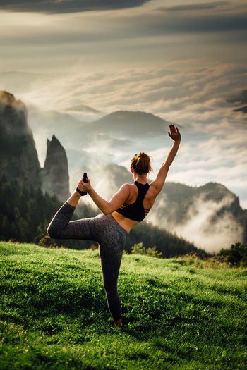 Rear view of woman exercising on mountain