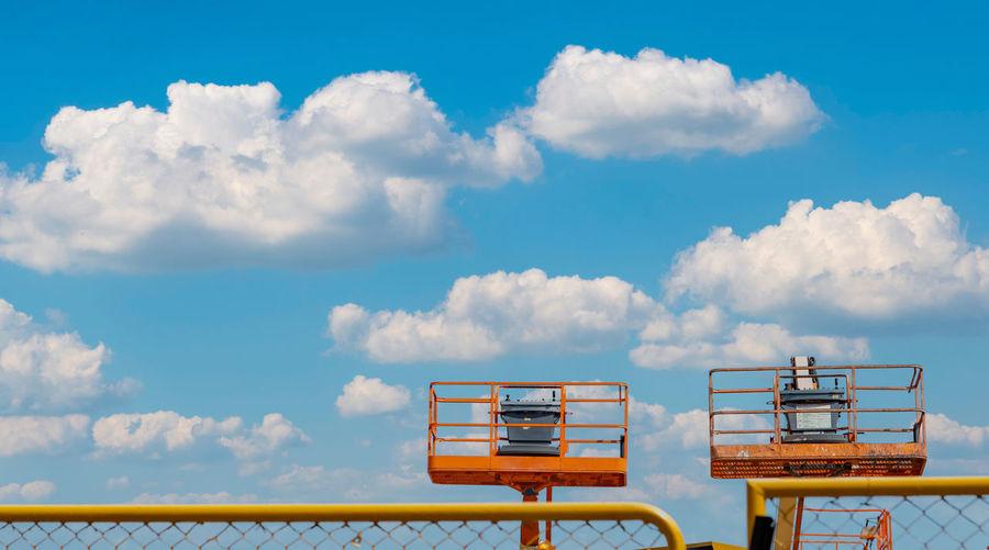 Articulated boom lift. aerial platform lift. telescopic boom lift against blue sky. mobile crane.