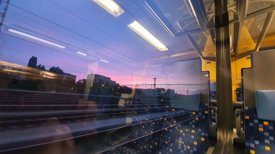 Blurred motion of tracks seen through moving train window during sunset