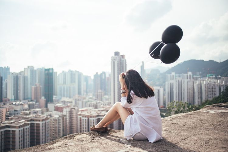 Woman Holding Black Balloons Looking At Cityscape