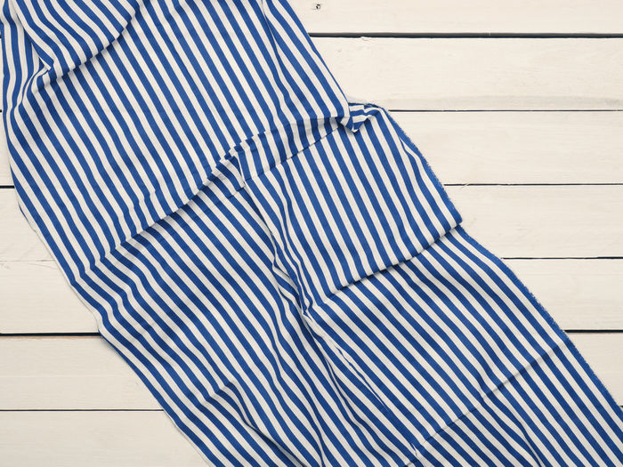 Table cloth on a wooden table, view from above Stripes Table Cloth Blue Casual Clothing Close-up Day Flooring High Angle View Leisure Activity Lifestyles Nature One Person Outdoors Pattern Real People Relaxation Striped Stripy Cat Sunlight Table View From Above White Color Wood Wood - Material