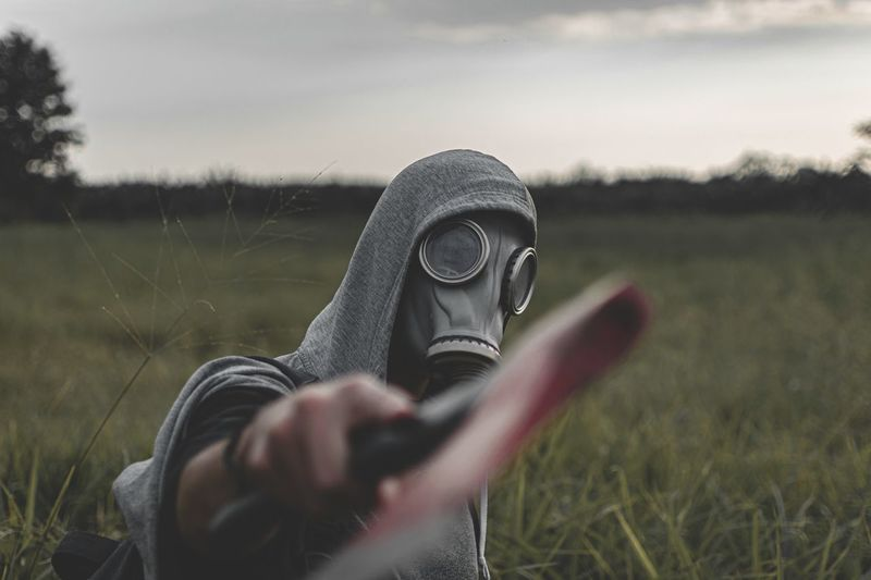 Man wearing gas mask holding axe on land