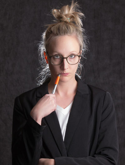Portrait of young woman holding eyeglasses against black background
