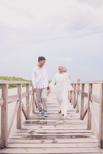 Couple standing on staircase against sky