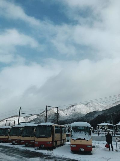 Train on snow covered mountain against sky