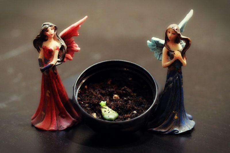 Angel Sculpture And Pot On Table