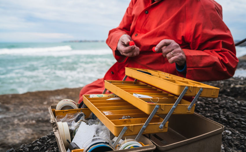 Midsection of man sitting by toolbox at beach