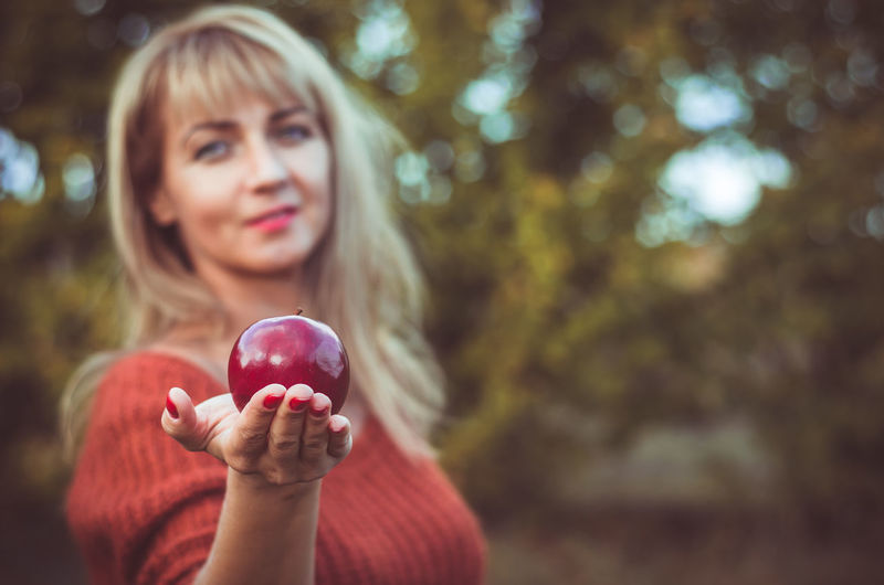 Blond woman holds a large red apple in her hand. Eva style. Seduction. Healthy food Beautiful Woman Hairstyle Hand Red Front View Adult Headshot Fruit Portrait Food Food And Drink Apple - Fruit Hair Blond Hair Outdoors Nature Tree Women Day Focus On Foreground One Person Holding Real People Lifestyles Leisure Activity Human Hand Young Adult