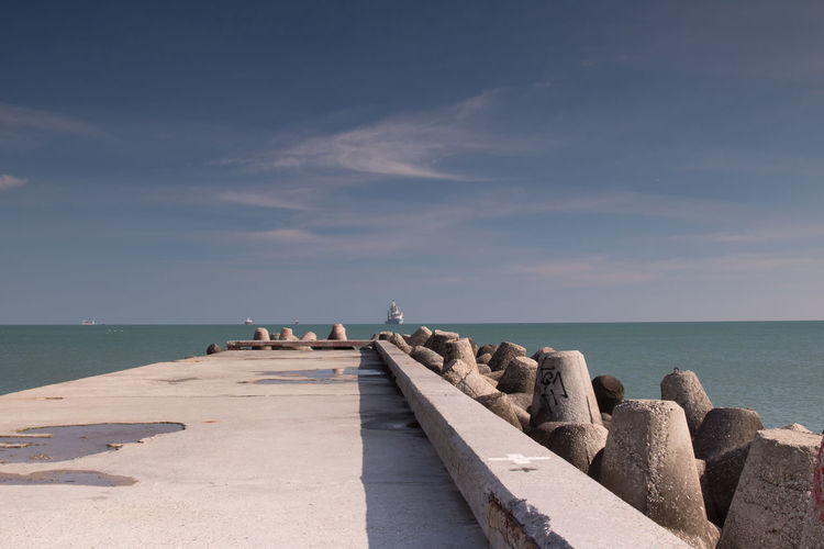 Pier by groynes against sea and sky