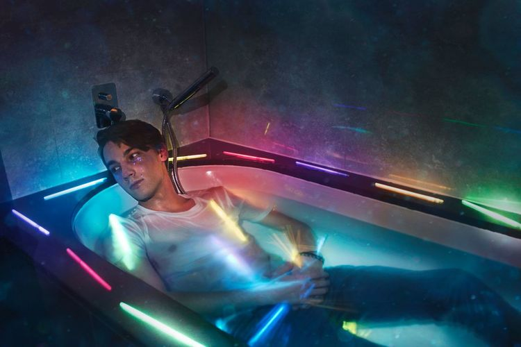 Digital composite image young man looking away while lying in illuminated multi colored bathtub