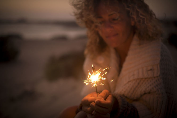 beautiful lady use and look a sparkly fire light in a summer night. beach and ocean defocused in the background. travel and vacation concept for a dreamer female middle age Beautiful Lady Kite In The Sky Adult Backgrounds Beach Burning Celebration Curly Hair Dark Firework Focus On Foreground Glowing Hairstyle Headshot Heat - Temperature Holding Illuminated Leisure Activity Lifestyles Motion Nature Night One Person Sparkler Sparks Women