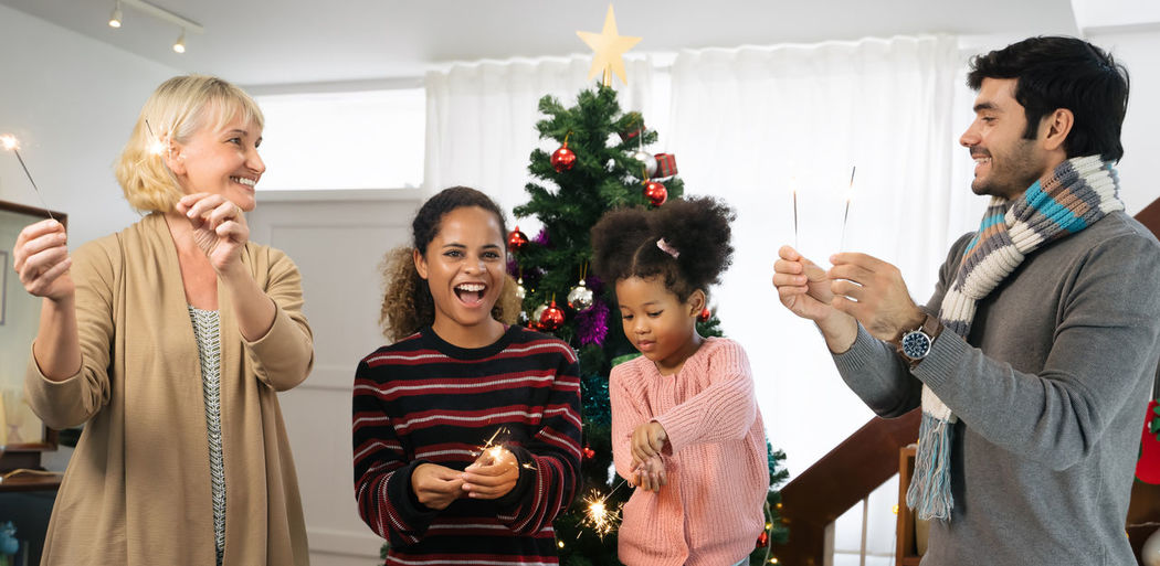 People holding illuminated sparklers while standing against christmas tree