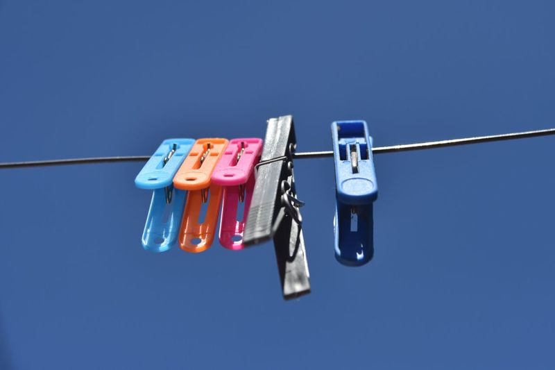 Low angle view of clothespins on clothesline against blue sky
